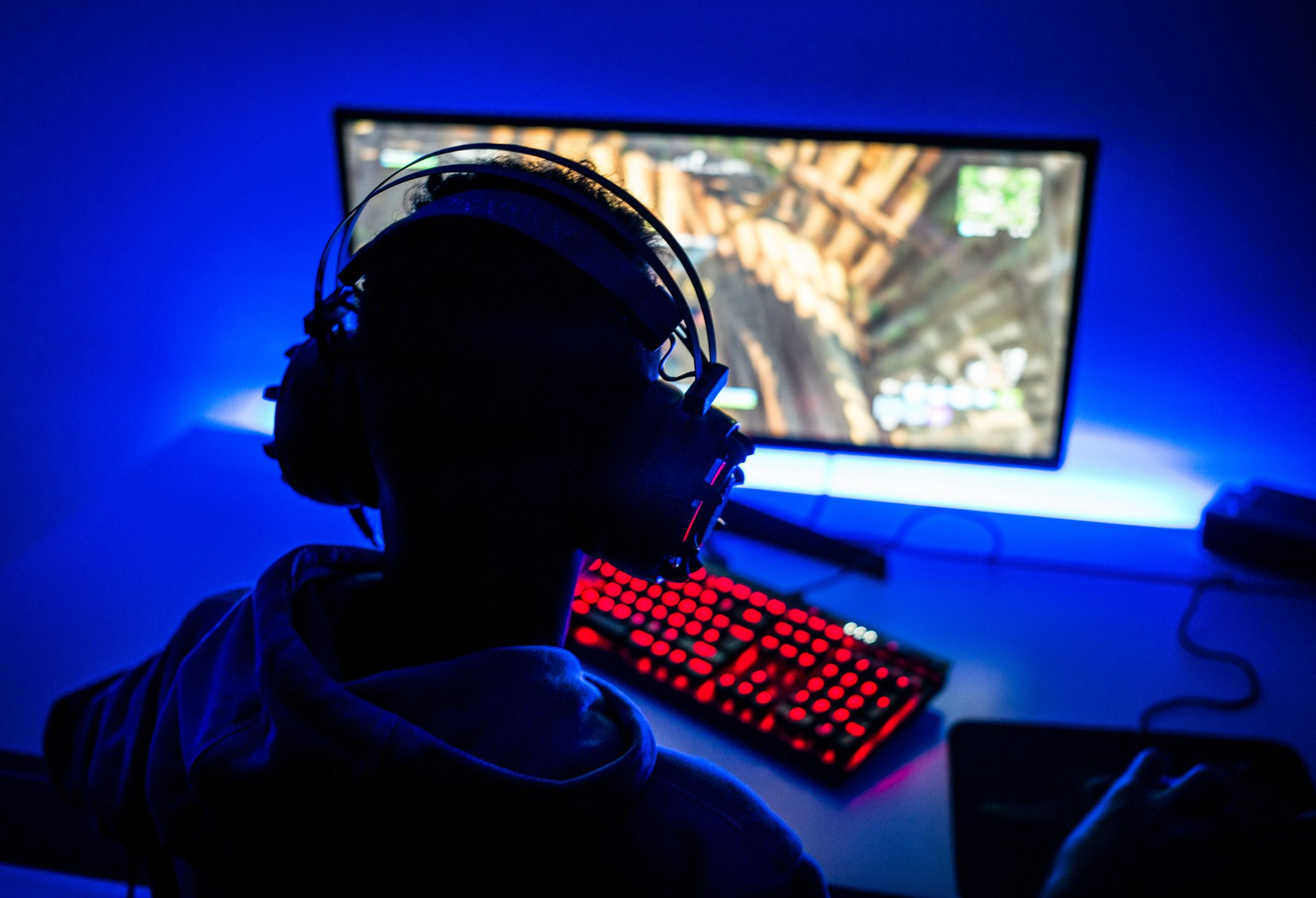 A boy playing video games on his gaming setup
