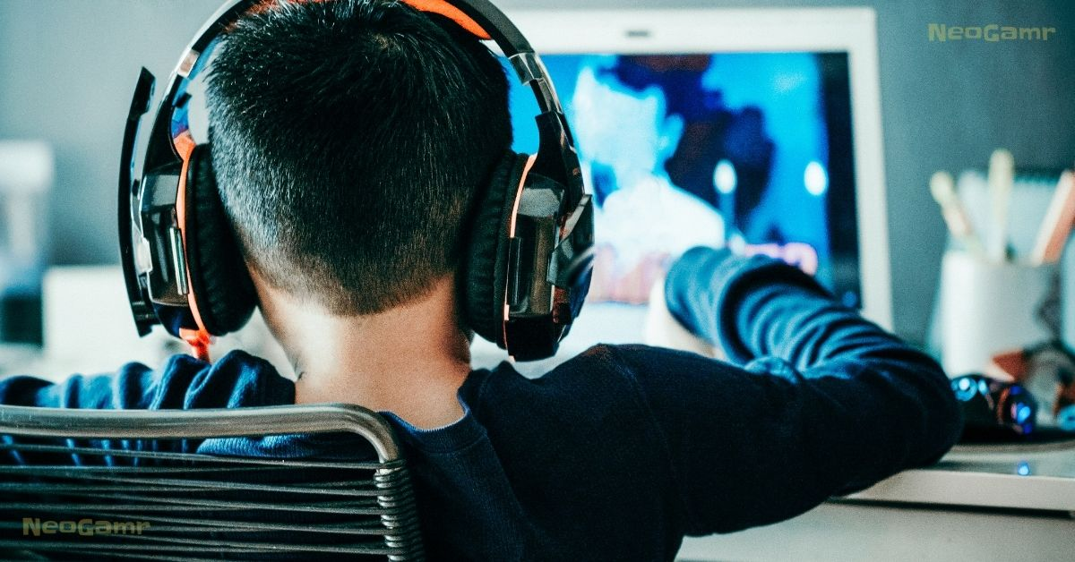 A boy wearing a gaming headset and playing video games